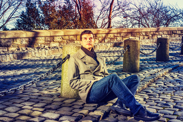 American Man traveling in New York, wearing gray woolen overcoat, blue jeans, black leather shoes, scarf, sitting on ground of vintage park, hopefully looking up. Color filtered effect