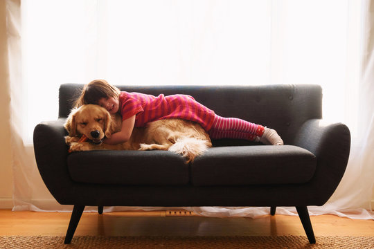 Young girl playing with dog on couch at home