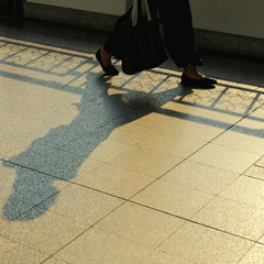 Alone woman walking with sunrise light and shadow go to business