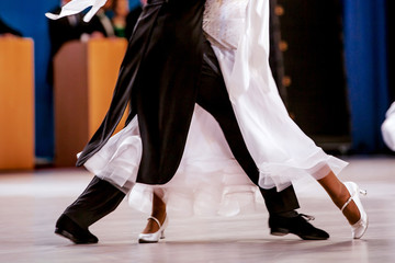 pair athletes dancers ballroom dancing. black tailcoat and white dress