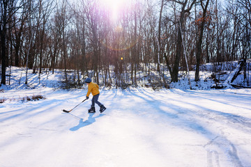 Young boy playing hockey on snowy landscape