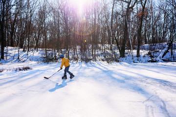 Boy playing ice hockey on ice rink
