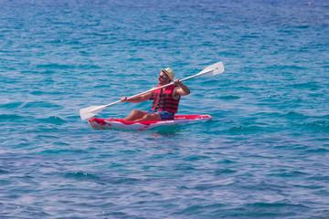 Man paddles a red kayak