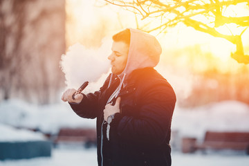 man is vape steam smoking an e-cigarette on the sunset. high contrast and monochrome color tone.
