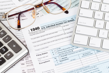 Tax form with calculator, glasses, and keyboard