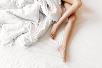 Slim, perfect and beautiful crossed woman legs on bed. Cropped image of erotically lying on bed beautiful woman in bedroom. Crumpled white bedclothes. Horizontal photo, top view.