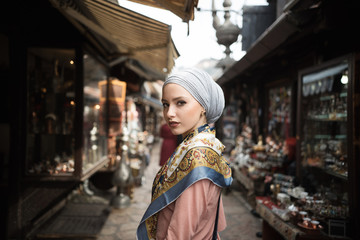 Woman wearing a headscarf standing in a bazar