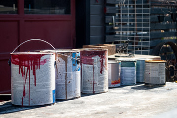 Old Paint Buckets Cans in front of an old garage