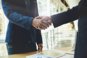 Business partnership meeting concept. Image business people shaking hands while sitting at the working place. Successful businessmen handshaking after good deal. Horizontal,