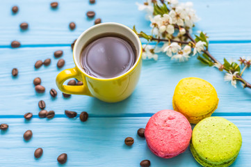 Stil life with macarons and coffee on the wooden background