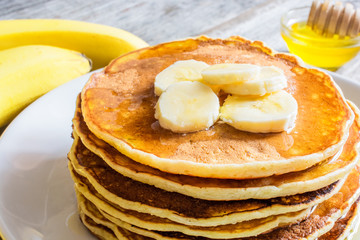 delicious pancakes with banana and honey over rustic wooden table