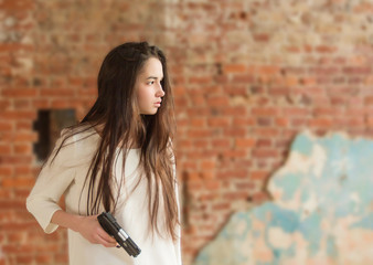 Young beautiful girl stands alone in a white shirt with a gun in her hand. Waiting for danger. Concept fear.