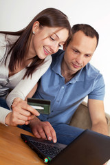 Couple shopping online, using credit card.