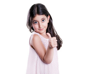 Beautiful happy little girl with long dark hair and dress looking at camera with thumbs up. studio shot, isolated on white background.