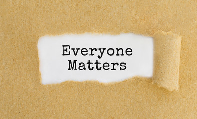 Text Everyone Matters appearing behind ripped brown paper.