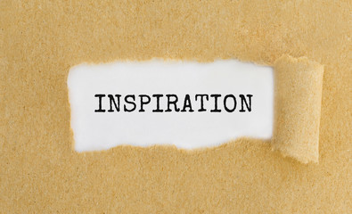 Text Inspiration appearing behind ripped brown paper.