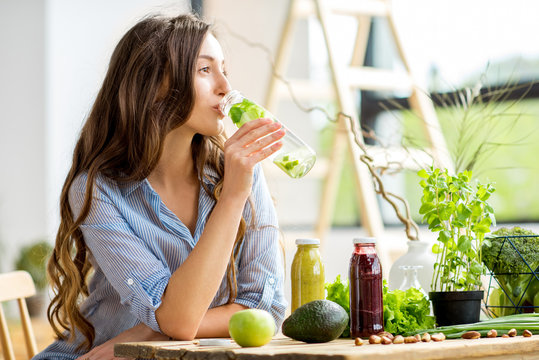 Beautiful woman sitting with drinks and healthy green food at home. Vegan meal and detox concept