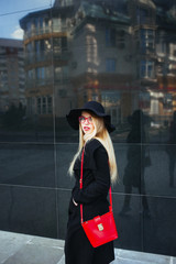 Beautiful young woman in a black coat and hat, wearing red glasses and a red bag walking in the city. Reflection of the city in the window