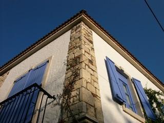 Weißes Eckhaus mit Mauerwerk aus Naturstein und blauen Fensterläden in der Altstadt von Alacati in der Provinz Izmir in der Türkei