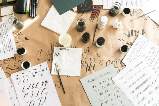 Calligraphy sheets, nibs, paper, ink and pens on a kraft background. Lettering calligraphy workshop. Letters of the English alphabet written with a paint brush. Concept hobby. top view, flat lay.