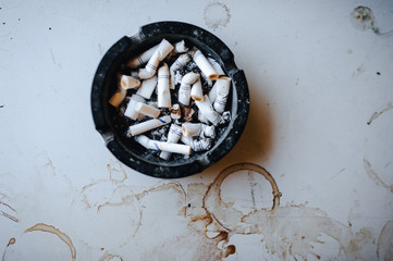 Ashtray with cigarette butts on the table.