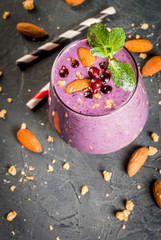 Healthy food. Dietary breakfast, snack. Berry smoothies with granola, black currant, blueberries and nuts almonds, decorated with mint. On a dark concrete table with ingredients, copy space