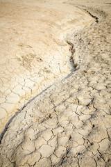 les traces d'un ruisseau asséché, au milieu d'une terre craquelée