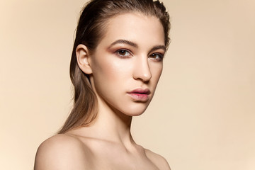 Beautiful woman face with natural make-up and wet hair on a beige  background with bare shoulders
