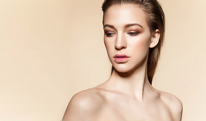 Beautiful model face with natural make-up and wet hair on a beige  background with bare shoulders