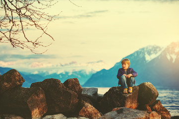One happy kid boy playing by lake Geneva at sunset with swiss mountains Alps on background. Image taken in Lausanne, Switzerland