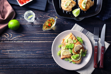 Plate of delicious tequila lime chicken with ingredients on wooden background