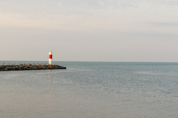 Wide angle view of a red and white lighthouse on Lake Ontario near Rochester, New York