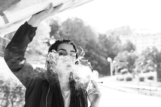 Braided young woman smoking outdoors. With african braids, pierced fashion woman. Converted to black and white, grain added.
