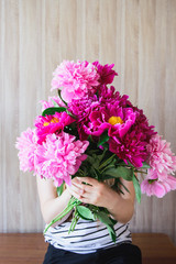 happy white caucasian young woman holding red and pink peonies bouquet in front of face at wood wall backdrop