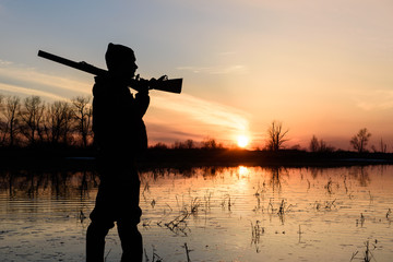Acrylic Prints Hunting Silhouette of a hunter at sunset in the water with a gun.