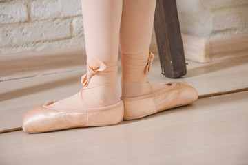 Ballerina legs first position in pointe, ballet dancer concept background. Classic ballet positions.a pair of ballerina's feet on an wood floor. satin ballet shoes
