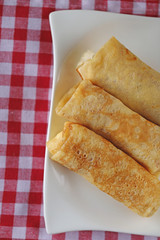 Three Stuffed pancakes on a white  plate On a checkered red white cotton napkin