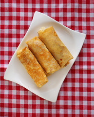 Three Stuffed pancakes on a white rectangular plate On a checkered red white cotton napkin