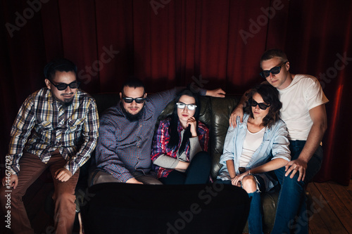 c5bae947c9d6 Company of five young friends in 3d glasses having fun. Youth group watch  tv sitting on couch at home in living room.