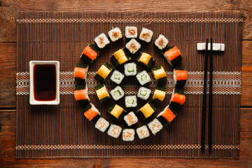 Japanese food art. Delicious uramaki rolls set, colorful round ornament of sushi served on brown straw mat, flat lay. Luxury restaurant menu photo.