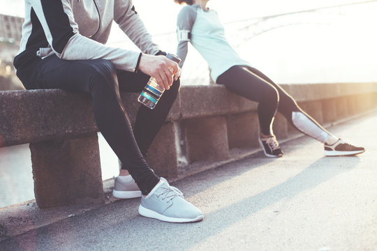 Group of athletes resting after workout session on the street. Tired man with bottle of water and woman relaxing on the bench