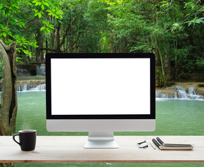 desktop computer white frame on work table and waterfall nature background