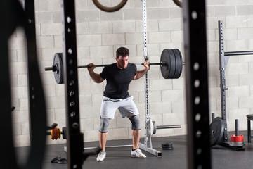 Bodybuilder exercising on squat rack
