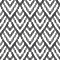 Vector illustration of the black and white colored ikat ornamental seamless pattern. Chevron design with scribble textured effect.