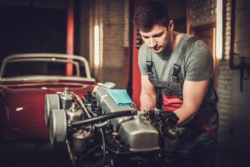 Mechanic working on classic car engine in restoration workshop