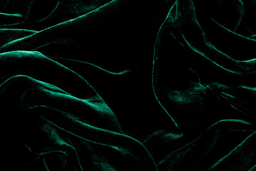 Dark green velvet background. Luxurious shiny material.