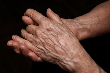 Folded senior woman wrinkled hands close up. Old age, age problems, poverty and loneliness theme
