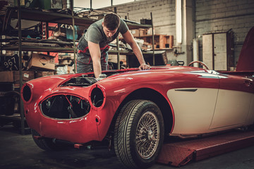 Mechanic working on classic car electrics in restoration workshop