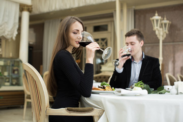 Beautiful woman and man drinking wine in restaurant