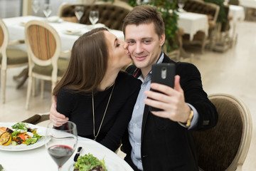 Beautiful couple taking selfie photo in a restaurant